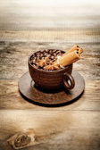 Wooden cup with coffee-beans on wooden table — Stock Photo