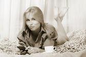 Frau auf dem bett liegend und mit handy und nehmen straftat — Stockfoto