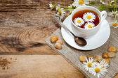 Herbal tea with chamomile on old wooden table — Stock Photo
