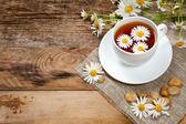 Chá de ervas com camomila na velha mesa de madeira — Fotografia Stock