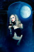 Vampire girl with glass of wine — Stockfoto