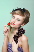 Woman with strawberry and bunch of grapes — Stock Photo