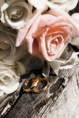 Bunch of flowers and gold rings on old wood — Stock Photo
