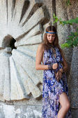 Woman in a sundress at the stone wall — Stock fotografie
