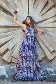 Woman in a sundress at the stone wall — Stock Photo