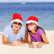 Beautiful couple in santa hats on tropical beach of Bali — Stock Photo #13822564