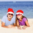Beautiful couple in santa hats on tropical beach of Bali — Stock Photo