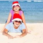 Beautiful couple in santa hats on tropical beach of Bali — Stock Photo #13822566