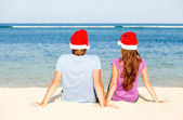 Beautiful coulpe in santa hats on tropical beach of Bali — Stock Photo