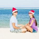 Beautiful couple in santa hats on tropical beach of Bali — Stock Photo #13889400