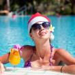 Beautiful girl in santa hat and sunglasses with fresh mango juic — Stock Photo #14220307