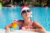 Beautiful girl in santa hat and sunglasses with fresh mango juic — Stock Photo