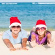 Foto de Stock  : Young couple in santa hats laughing on tropical beach. new year