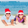 图库照片: Young couple in santa hats laughing on tropical beach. new year