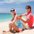 Beautiful young couple sitting and having fun on beach — Stock Photo #14634491