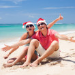 Young couple in santa hats laughing on tropical beach. new year — Stock Photo #14634553