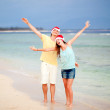 Young couple in santa hats laughing on tropical beach. new year — Stock Photo #14634979