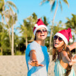 Young couple in santa hats laughing on tropical beach. new year — Stock Photo #14880865