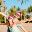 Young couple in santa hats laughing on tropical beach. new year — Stock Photo #14880897