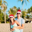 Young couple in santa hats laughing on tropical beach. new year — Stock Photo #14880915