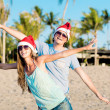Young couple in santa hats laughing on tropical beach. new year — Stock Photo