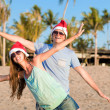 Young couple in santa hats laughing on tropical beach. new year — Stock Photo #14880943