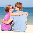 Beautiful young couple sitting and having fun on beach — Stock Photo #14880969