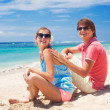 Beautiful young couple sitting and having fun on beach — Stock Photo #14881027