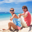 Beautiful young couple sitting and having fun on beach — Stock Photo #14881031