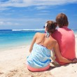 Beautiful young couple sitting and having fun on beach — Stock Photo #14881045