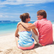 Beautiful young couple sitting and having fun on beach — Stock Photo #14881061