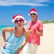 Young couple in santa hats laughing on tropical beach. new year — Foto de Stock
