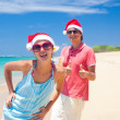 Young couple in santa hats laughing on tropical beach. new year — Stockfoto