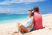 Beautiful young couple sitting and having fun on beach — Stock Photo
