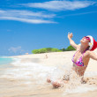 Young woman in santa hat laughing at beach, christmas, new year — Stock Photo #15795897