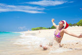 Young woman in santa hat laughing at beach, christmas, new year — Stock Photo