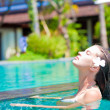 Half face portrait of beautiful woman in luxury pool — Stock Photo #16079723
