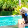 Back view of beautiful woman in straw hat in luxury pool — Stock Photo #16079733