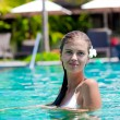 Portrait of young attraactive smiling woman in luxury pool — Stock Photo #16079821