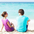 Beautiful young couple sitting and having fun on beach — Stock Photo