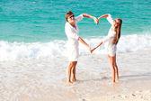 Młoda szczęśliwa para zabawy na tropikalnej plaży. miesiąc miodowy — Zdjęcie stockowe