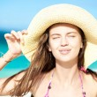 Happy young woman smiling in straw hat with closed eyes on the beach — Stock Photo #18984253