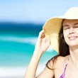 Happy young woman smiling in straw hat with closed eyes on the beach — Stock Photo #18984261