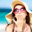 Beach Portrait of young woman in sunglasses and hat blowing kiss — Stock Photo #18984269