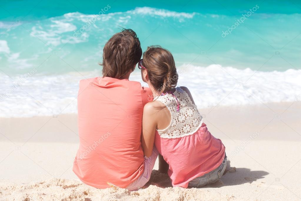 Beautiful young couple sitting and having fun on beach — Stock Photo #18984221