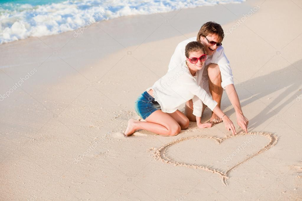 Portrait of young happy couple drawing a heart on the sand — Stock Photo #18984271