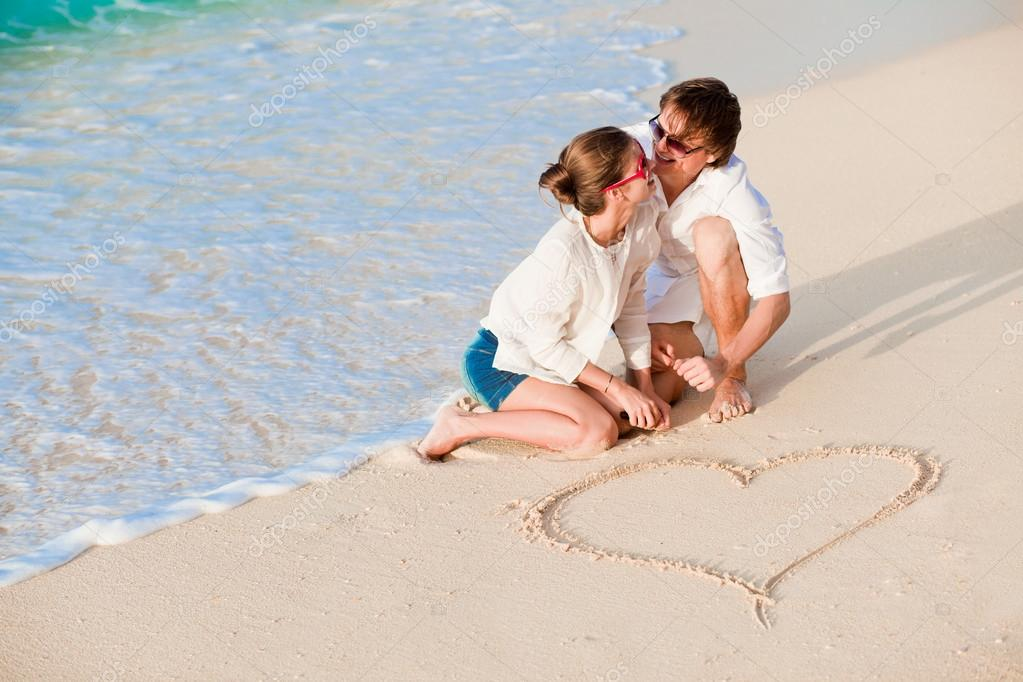 Portrait of young happy couple drawing a heart on the sand  Stock Photo #18984279