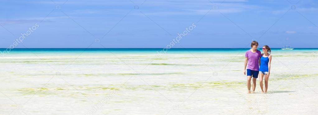 Happy yong couple walking on the beach — Stock Photo #18984515