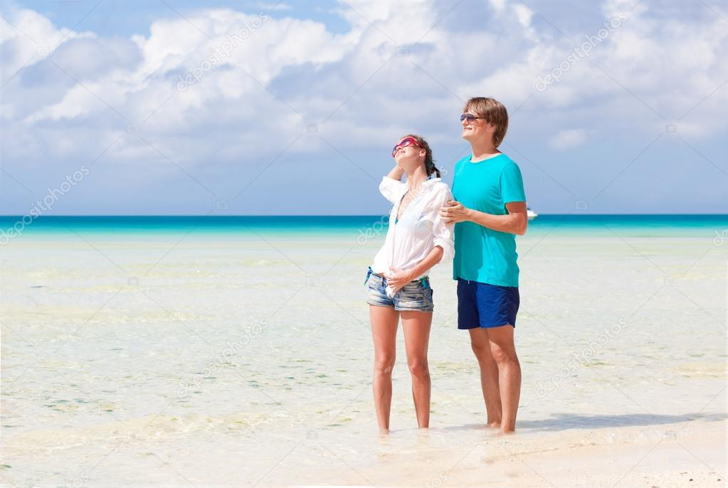 Happy yong couple walking on the beach — Stock Photo #18985599