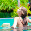 Back view of beautiful woman in straw hat in luxury pool — Stock Photo #19289079
